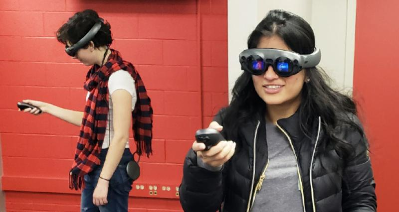 two women wearing mixed reality headsets
